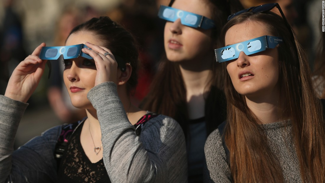 People use special glasses near the Brandenburg Gate in Berlin.