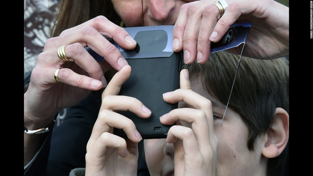 People try to take a picture of the eclipse with a smartphone in Toulouse, France.