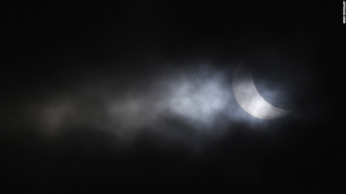 The eclipse is visible through a break in the clouds above Gateshead, England.