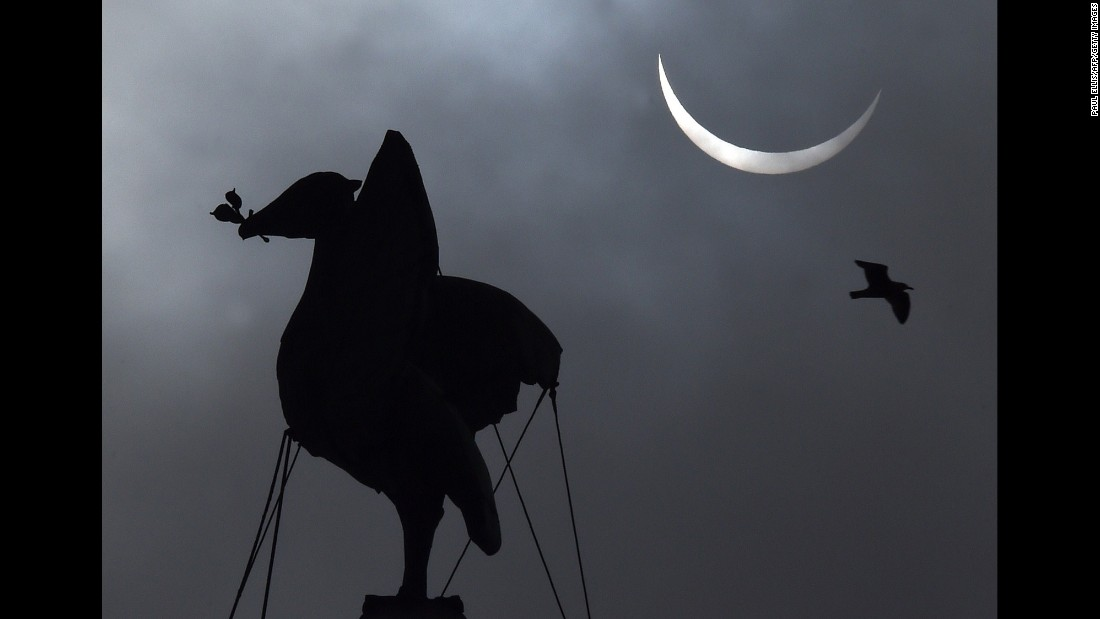 The eclipse forms above the Liver Bird on top of the Liver Building in Liverpool, England.