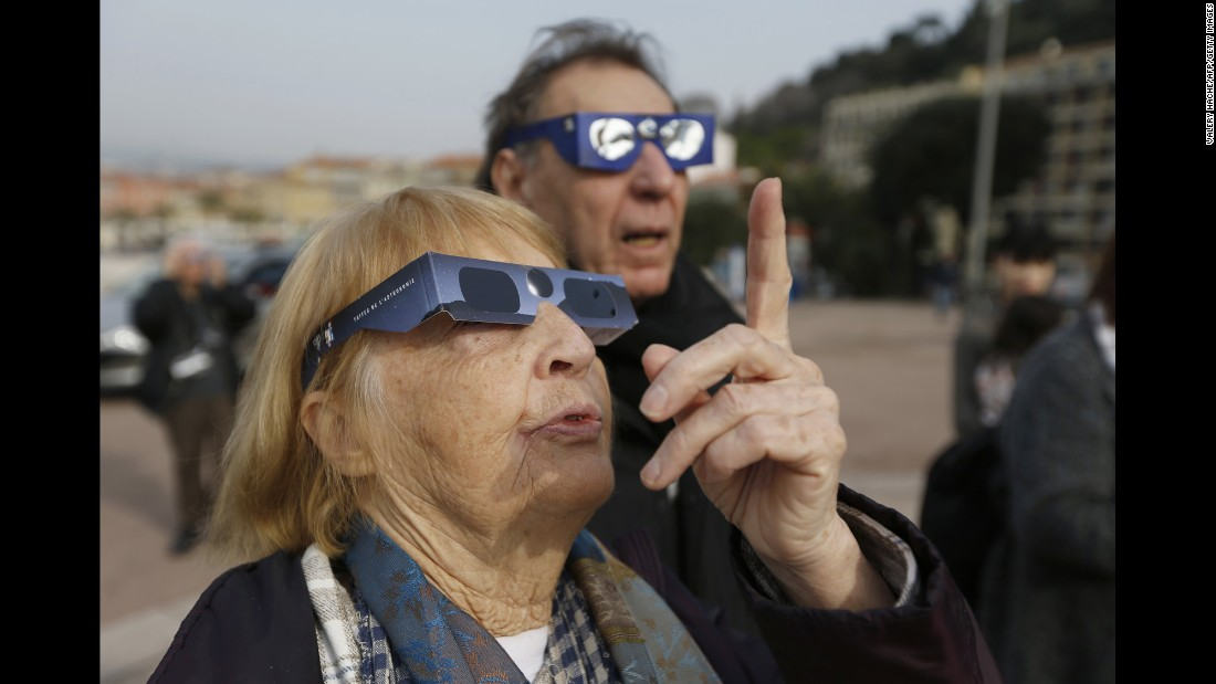 People in Nice, France, use protective glasses to watch the eclipse.