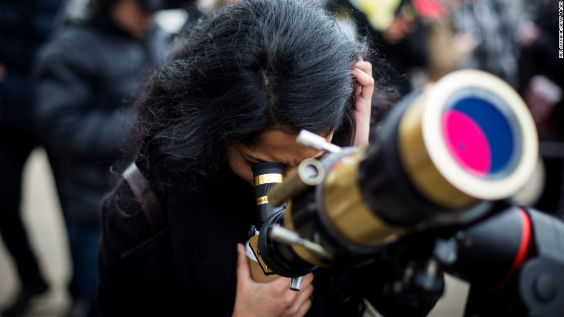 A woman looks through a telescope outside the Royal Observatory, Greenwich, in London.