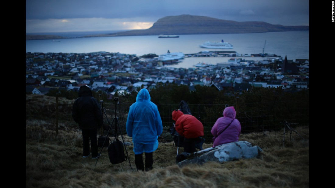 People wait for the start of the eclipse on a hill overlooking the sea and Torshavn, the capital of the Faroe Islands, between Scotland and Ireland.