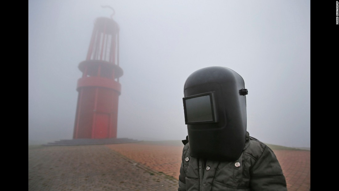 A boy wearing his father's welding mask gets disappointed after fog blocks the solar event from being viewed in Duisburg, Germany.