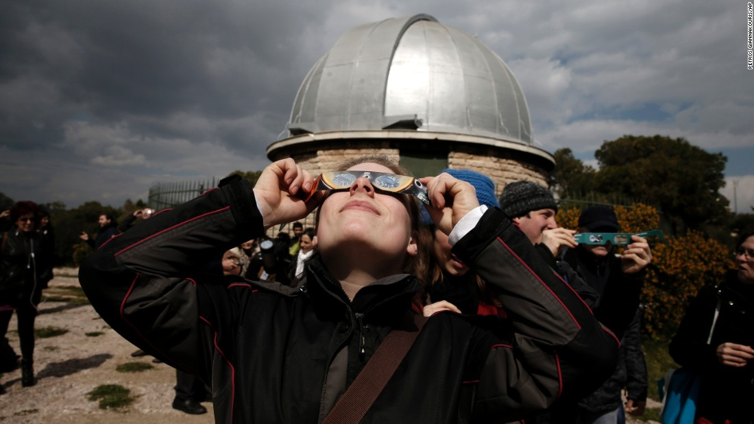 A woman looks at the eclipse through special glasses at the National Observatory of Athens in Greece.