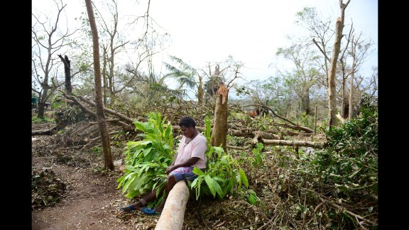 """A woman sits on a fallen tree among what's left of her garden in Port Vila, Vanuatu, on Thursday, March 19, nearly a week after Cyclone Pam ripped through the island nation in the South Pacific. Vanuatu President Baldwin Lonsdale has called the storm a """"monster,"""" saying it has set back the development of his country, already one of the poorest in the region, by years."""