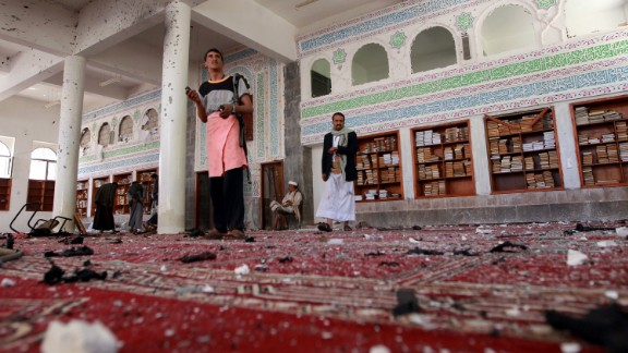 Armed men inspect damage after an explosion at the Al Badr mosque in Sanaa on Friday, March 20.