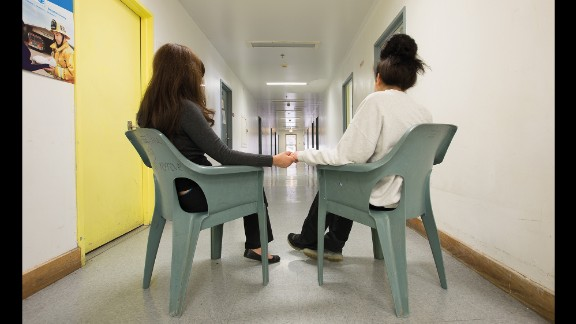A mother visits her daughter in a hallway at a juvenile detention center in Los Angeles.