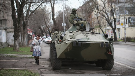 A woman walks past a Russian military personnel carrier outside a Ukrainian military base on March 18, 2014 in Simferopol, Ukraine. Voters on the autonomous Ukrainian peninsular of Crimea voted overwhelmingly to secede from their country and join Russia.