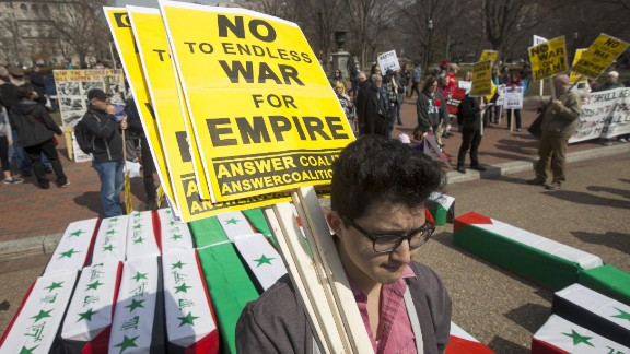 Demonstrators protesting U.S. military involvement overseas carry signs amid mock coffins outside the White House on Saturday.