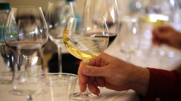 """File - In this May 20, 2009 file photo a glass of white wine is swirled during a tasting in Oakville, Calif. More than two dozen California vintners are facing a lawsuit claiming their wines contain dangerously high levels of arsenic. The industry group Wine Institute dismissed the allegations as """"false and misleading."""" (AP Photo/Eric Risberg, File)"""