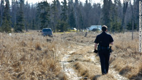 A police officer walks to a temporary camp where officials are working to identify remains of what Kenai police think are a family missing since May.