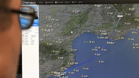 A man in Madrid looks at a monitor with a map, released from the Flightradar24 website, showing the point where the plane