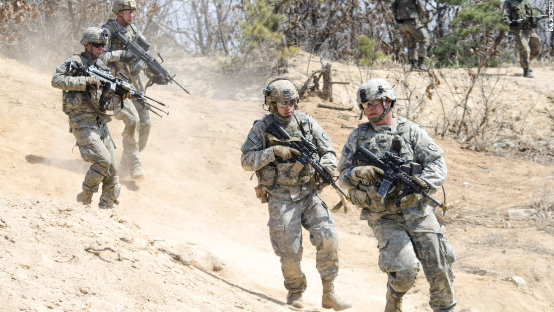 U.S. soldiers look for cover during drills in open terrain.
