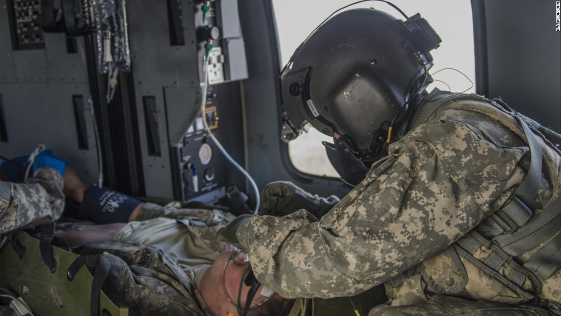 Soldiers tend to an injured soldier inside a helicopter.