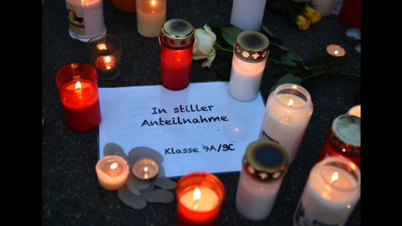 """Candles sit on a paper reading """"In silent memory, Class 9A/9C"""" in front of the Haltern high school on March 24."""