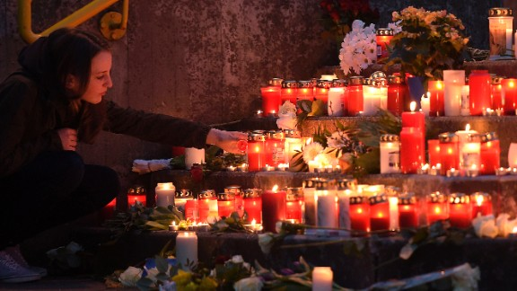A student lights a candle in front of Joseph-Koenig Gymnasium on March 24.