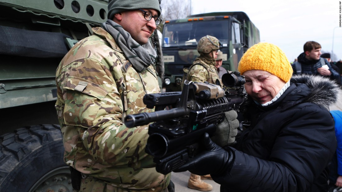 A member of the 2nd Cavalry Regiment shows a gun to a woman on Monday, March 23, in Salociai, north of the Lithuanian capital of Vilnius.