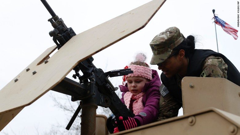 A soldier shows a gun to a young girl in Salociai on March 23.