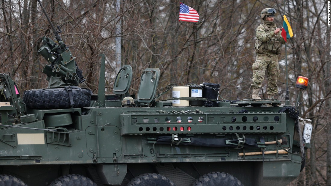 A U.S. soldier raises the Lithuanian flag on a Stryker vehicle on March 23 in Salociai.