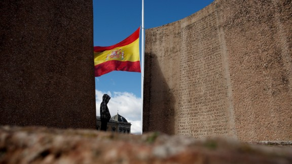 A person in Madrid stands near a Spanish flag flying at half-staff on March 25.