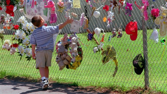A boy visits the fence that surrounds the remains of the Federal Building in May 1997. It was later razed, and a park and memorial was built on the site.