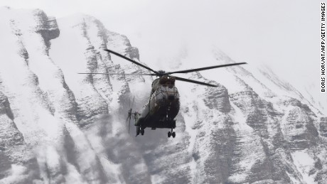 A helicopter flies near Seyne, south-eastern France, on March 25, 2015, near the site where a Germanwings Airbus A320 crashed in the French Alps. A German airliner crashed near a ski resort in the French Alps on March 24, killing all 150 people on board.