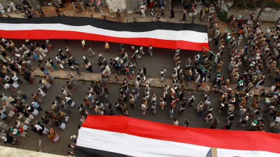 "Houthi supporters in Sanaa deploy giant national flags Wednesday, March 18, during a demonstration to mark the fourth anniversary of the ""Friday of Dignity"" attack. In 2011, forces loyal to Saleh opened fire on protesters who had gathered in Sanaa to demand the ouster of Saleh and his regime."