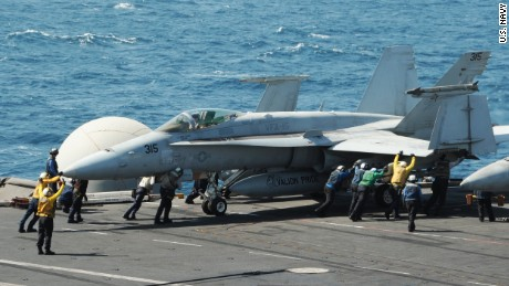 An F/A-18C Hornet is guided on the flight deck of the aircraft carrier USS George H.W. Bush  on August 8, 2014 in the Arabian Gulf.