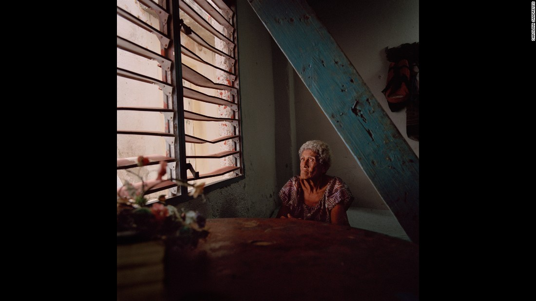 "A woman sits by a window in the Casablanca neighborhood of Havana, Cuba. Photographer Carolina Sandretto spent some time in ""solares,"" the crumbling maze-like buildings that many Cubans divide and cohabitate."
