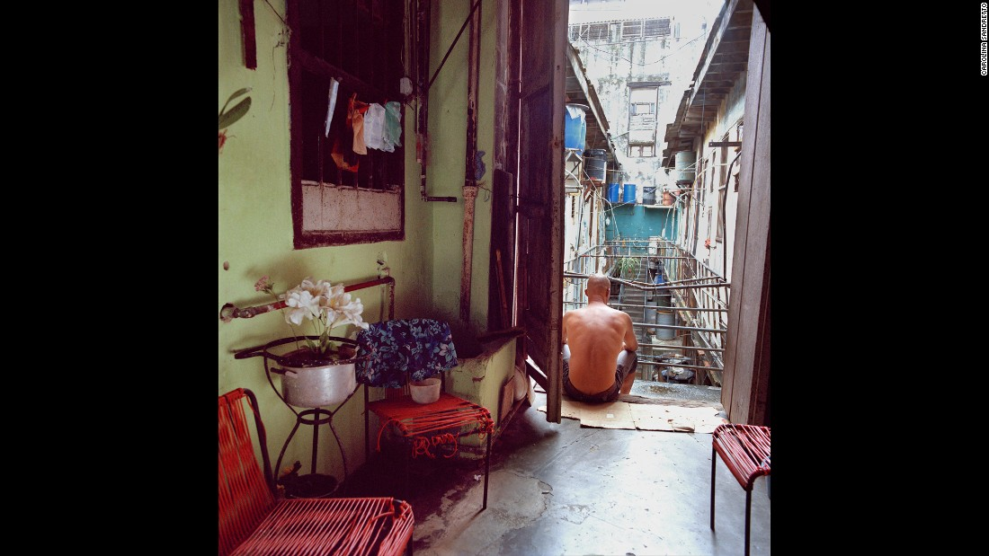 A man sits in the doorway of a communal living house.