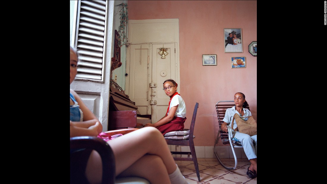A young girl has a piano lesson in Havana. In solares there are often several generations and separate families sharing one dwelling.