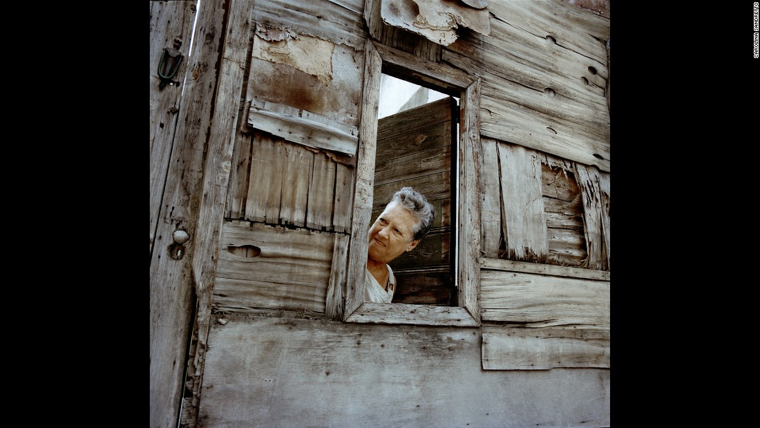 A woman looks out from a solar in Havana.