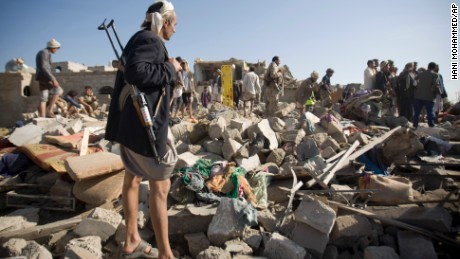 A Houthi Shiite fighter stand guard as people search for survivors under the rubble of houses destroyed by Saudi airstrikes near Sanaa Airport, Yemen, Thursday, March 26, 2015. Saudi Arabia launched airstrikes Thursday targeting military installations in Yemen held by Shiite rebels who were taking over a key port city in the country's south and had driven the embattled president to flee by sea, security officials said. (AP Photo/Hani Mohammed)