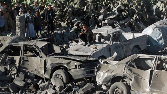 People gathered around burned vehicles after Saudi-led airstrikes against the Houthis near Sanaa Airport on March 26.