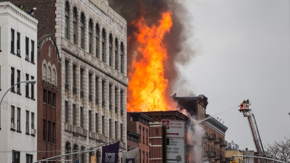 Flames can be seen coming from the building's roof.