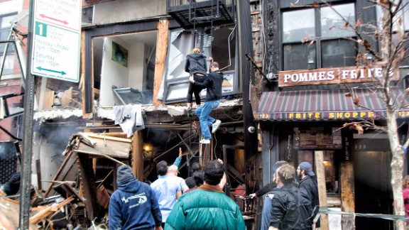 "People climb down a fire escape at the scene of the explosion. Luca Babini, the iReporter who took this photo, said he was in his office less than a block away at the time of the blast. He said a man immediately climbed a fire escape in an attempt to rescue people. ""I saw a lot of people lined up at the streets trying to help,"" he said."
