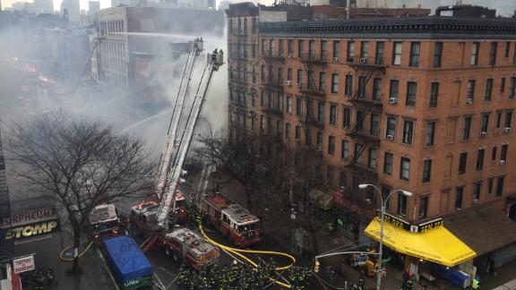 Smoke billows as firefighters fill the street below.