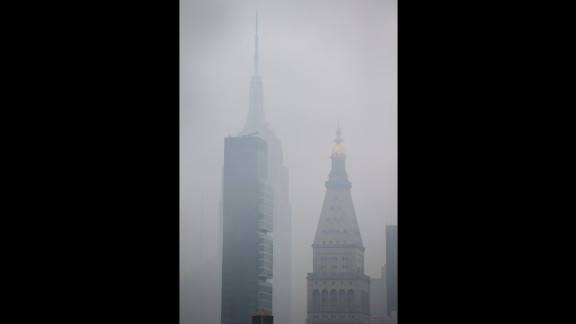 The Empire State Building can be seen through the smoke caused by the fire.