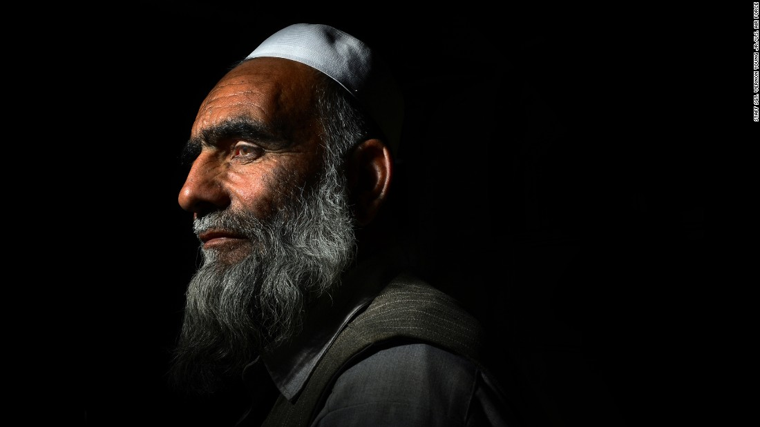 An Afghan man spends a moment alone in a military planning room before serving tea to soldiers on June 11, 2014.