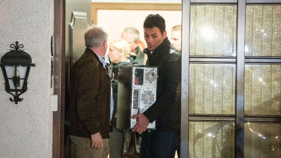 Investigators carry a computer from the home of Lubitz