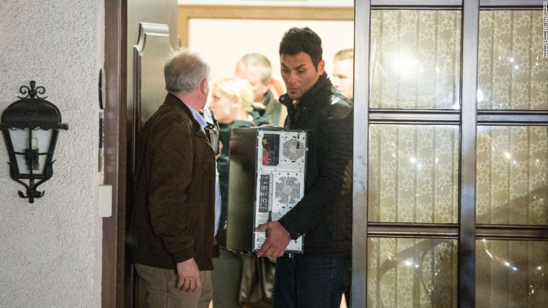 Investigators carry a computer from the home of Lubitz's parents in Montabaur, Germany, on Thursday, March 26.