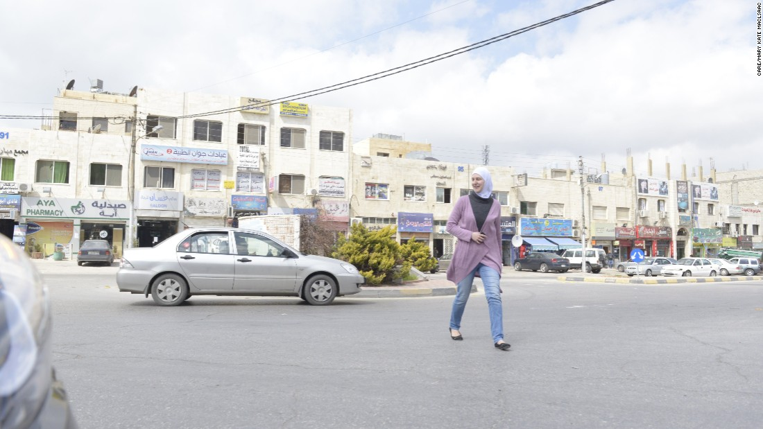 Hiba crosses a street in the north Amman suburb. She is focused on finishing her education despite being a refugee for the past four years.