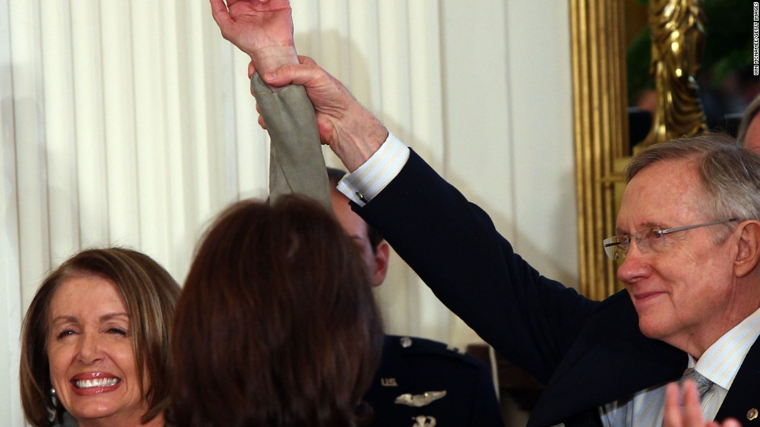 Pelosi and Reid throw their hands up as Obama introduces them during the signing ceremony for the Affordable Health Care for America Act in the East Room of the White House on March 23, 2010.