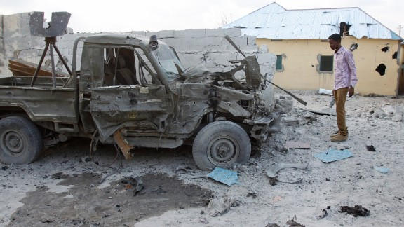 A man stands near the wreckage of the vehicle that carried the bomb, which was detonated at the hotel's gate.