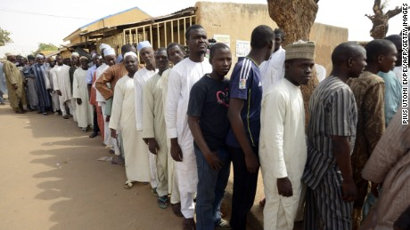 Men wait in line on March 28, 2015 outside a polling station in Gidan Niyam Sakin Yara in Daura in Katsina State. Polling stations opened in Nigeria on March 28, the electoral commission said, as voters went to the polls to elect a new president in what is being seen as the closest campaign in the country's history.