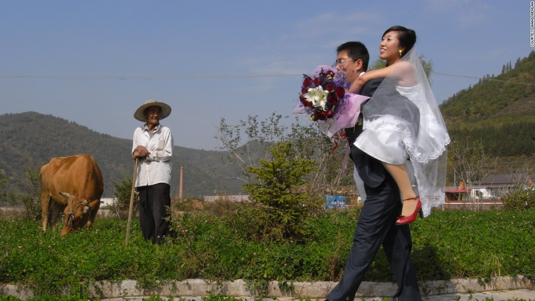 A groom carries his bride through a field in Baishan, Jilin province in 2007 as an old man looks on. Wang's work often reveals the clashes between tradition and modernity in China.