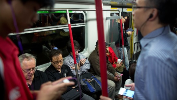 In Hong Kong, rates of myopia are as high as 87%. This shows bespectacled passengers in Hong Kong riding the subway.
