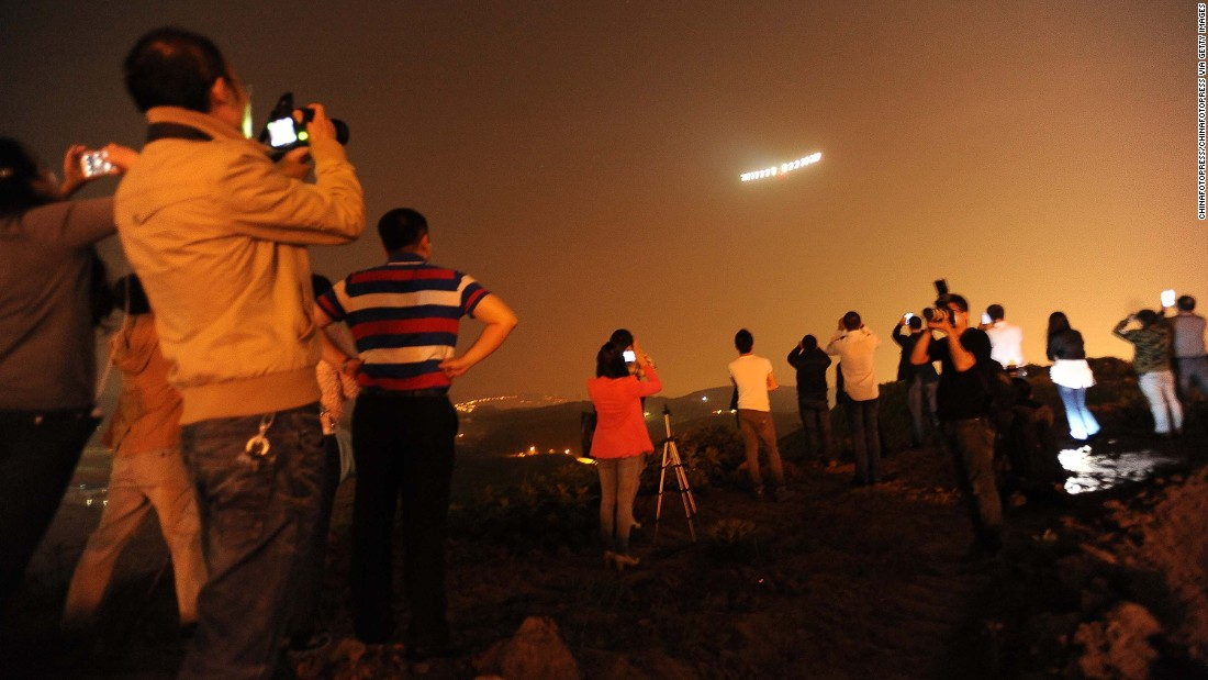 MARCH 31 - CHONGQING, CHINA: People take photos of the solar-powered aircraft Solar Impulse 2 at Chongqing Jiangbei International Airport. The aircraft, the first to be completely sustained by the sun's rays, took off from Mandalay, Myanmar's second biggest city, early Monday. It is the fifth flight of a landmark journey to circumnavigate the globe.