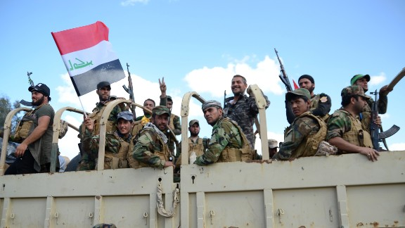 "Shiite fighters from the Popular Mobilisation units celebrate on a truck inside the northern Iraqi city of Tikrit on March 31, 2015 during a military operation to retake it from the Islamic State (IS) group. Prime Minister Haider al-Abadi Prime Minister said security and allied forces backed by US-led coalition aircraft ""liberated"" Tikrit, 80 miles (130 kilometers) north of Baghdad, the country's biggest victory yet in the fight against IS jihadists.    AFP PHOTO / STR        (Photo credit should read -/AFP/Getty Images)"